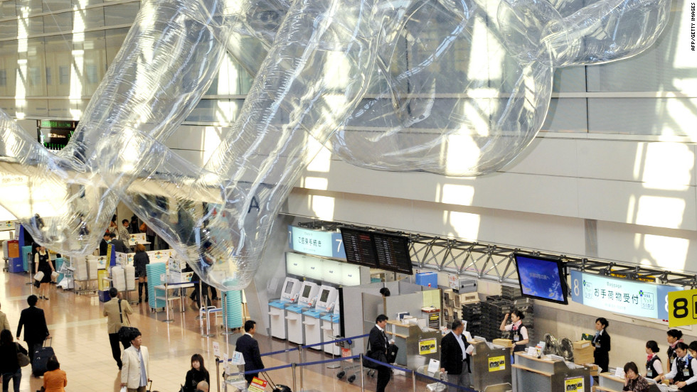 A human-shaped plastic balloon floats in the air above the concourse of Tokyo's Haneda Airport as part of a temporary public art installation in March 2009.