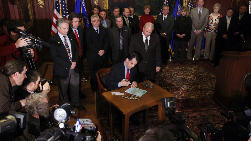 On March 11, 2011, Walker signs a bill that ends the collective bargaining rights of public employees as a measure to close the state's budget shortfall.