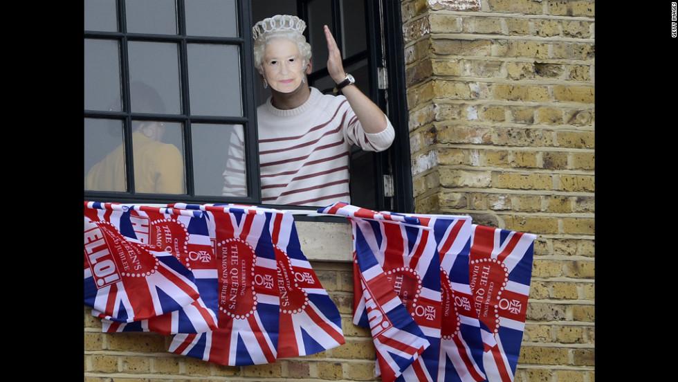 A woman wearing a mask of Queen Elizabeth II waves from a window near Tower Bridge.