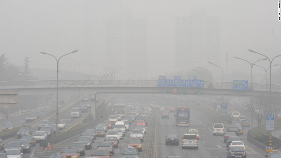 Vehicles making their way along a road on a smoggy day in Beijing on January 18, 2011.