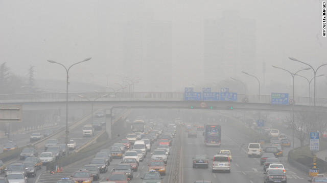 Vehicles make their way along a road on a smoggy day in Beijing.