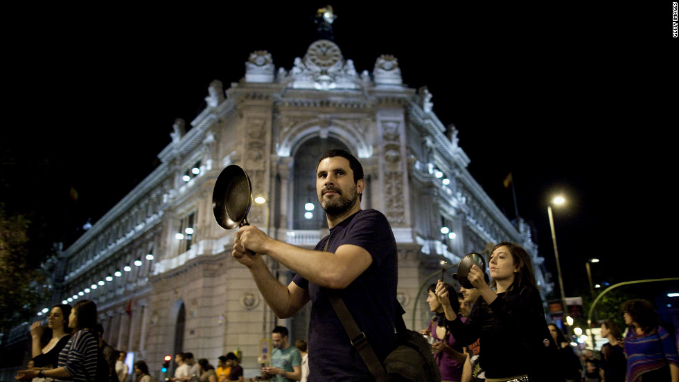A protester hits a pot while walking past the Bank of Spain on May 15, 2012 in Madrid, Spain. Spain's 'Indignants' prepared events across Spain to mark the anniversary of their movement.