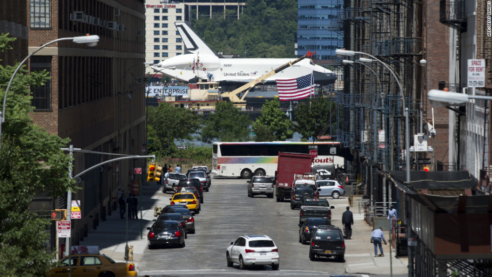 The Enterprise is seen from a busy New York street as it is carried up the river Wednesday.