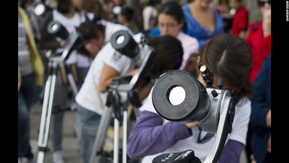 Astronomy students in Mexico City look at the sun through telescopes.