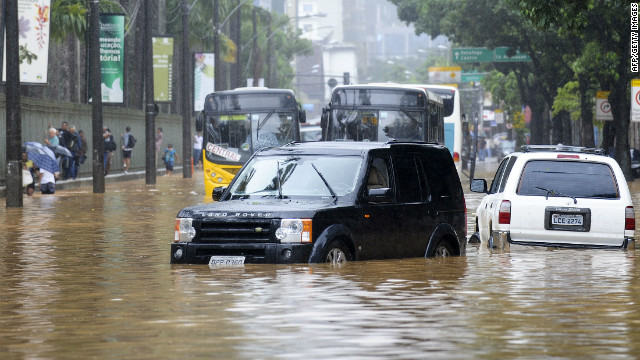 Vehicles remain stranded or blocked in a flooded street of Rio de Janeiro, on April 6, 2010. Flooding from torrential rains and deadly mudslides claimed at least 77 lives in Brazil's Rio de Janeiro state, authorities said Tuesday. Civil defense officials said about half of the fatalities occurred in Rio de Janeiro city, where authorities urged residents to remain indoors and not venture downtown, where streets were impassable. AFP PHOTO/ANTONIO SCORZA (Photo credit should read ANTONIO SCORZA/AFP/Getty Images)