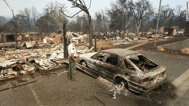 Senior Wildlife Officer Geoff McClure looks over the destruction in the main street of Marysville, some 100 kilometres northeast of Melbourne on February 9, 2009 after raging Australian wildfires left at least 131 people dead amid a landscape of charred homes, bodies and devastated communities. The wildfires have become the deadliest in Australia's history, destroying entire towns and wiping out families and amid the heartache there was also anger as police revealed they suspected some of the fires were started by arsonists, whom Prime Minister Kevin Rudd accused of 'mass murder.' AFP PHOTO/William WEST (Photo credit should read WILLIAM WEST/AFP/Getty Images)