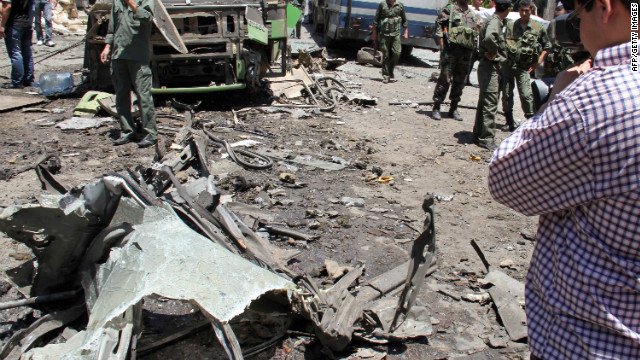 Syrian security forces inspect the scene of an explosion that targeted a military bus in Damascus.