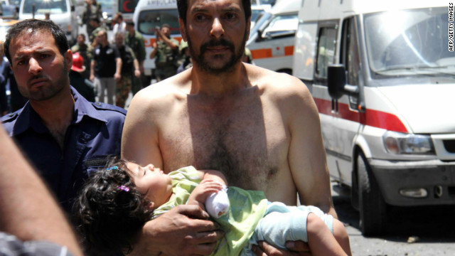 A Syrian man carries a wounded girl after an explosion targeted a military bus on June 8, 2012.
