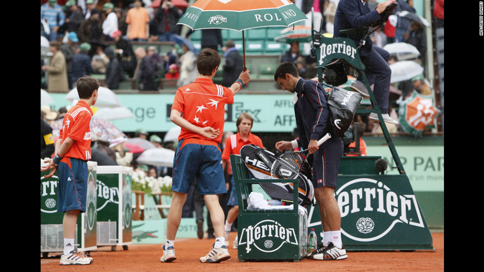 Djokovic leaves the court for a rain delay during the third set after officials haulted play during a downpour. The match was delayed a second time in the fourth set and finished Monday.