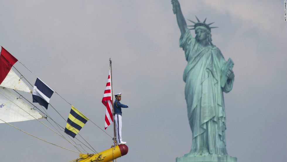 "Sailors aboard the Indonesian tall ship ""Dewaruci"" sail past the Statue of Liberty during Fleet Week in May 2012."