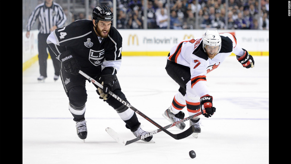 The Kings' Dwight King and the Devils' Henrik Tallinder battle for control of the puck.