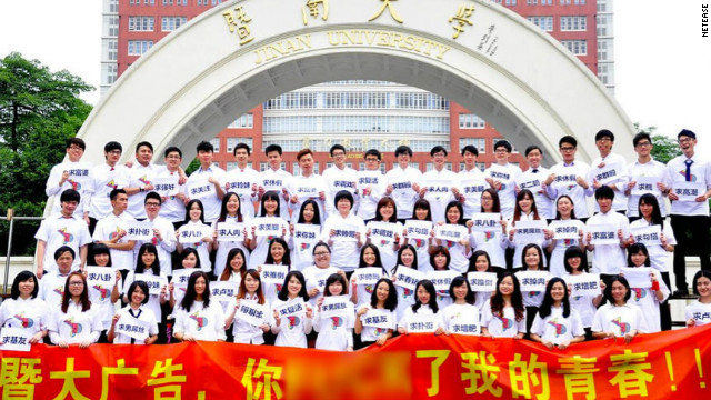 "Students stand in front of a banner that reads ""Jinan University Advertising Department, you f***ed my youth!"""