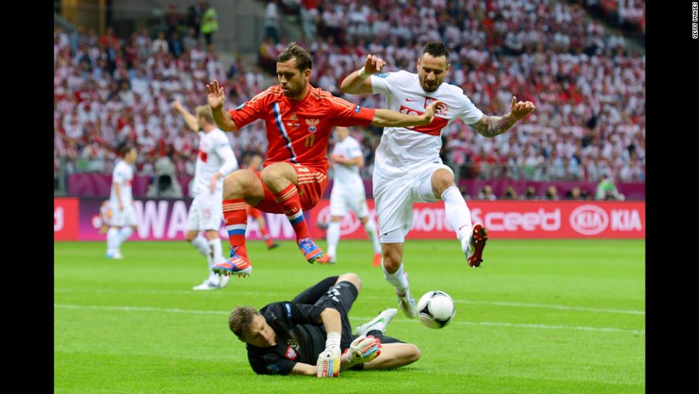 Aleksandr Kerzhakov of Russia and Marcin Wasilewski of Poland jump to avoid colliding with Poland's goalkeeper, Grzegorz Sandomiersk.