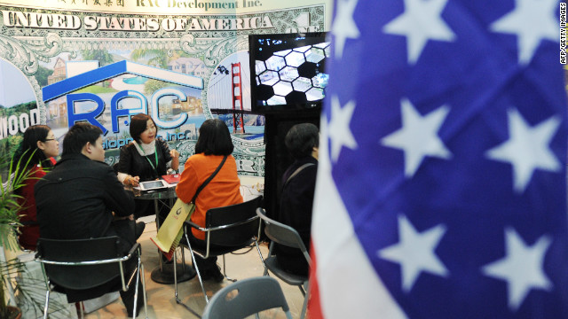 Potential Chinese real estate investors look at a display of United States property for sale at the Overseas and China Property Expo in Beijing on April 5, 2012.
