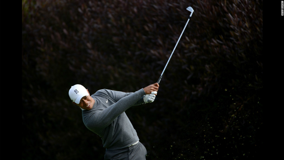 Woods, who was leading his group, hits his tee shot on the 13th hole Thursday.