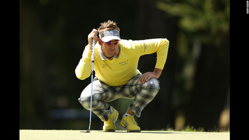 Ian Poulter of England lines up a putt during the first round.