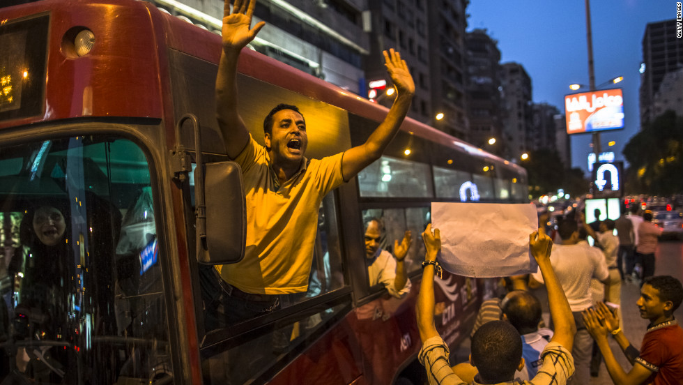 A bus driver stops to wave in support of Egyptian protesters making their way to Tahrir Square on Thursday.