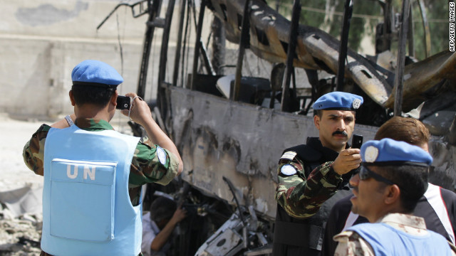 U.N. observers photograph a bus bombed outside a Shiite holy shrine in the Syrian capital, Damascus, on June 14.