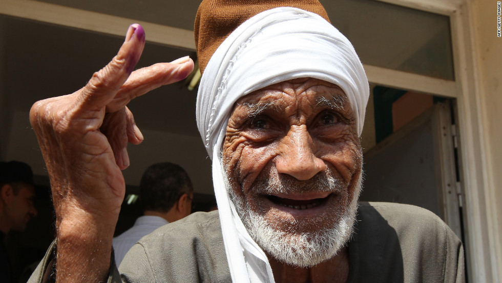 An elderly Egyptian man shows the indelible ink stain on his finger after voting on the first day of the second round of the historical presidential election at a polling station in the city of Zagazig.