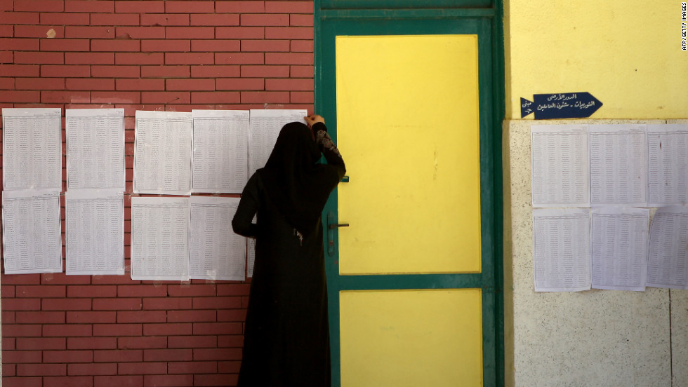 A veiled Egyptian woman looks for her name on the registered voters' list in the city of Zagazig.