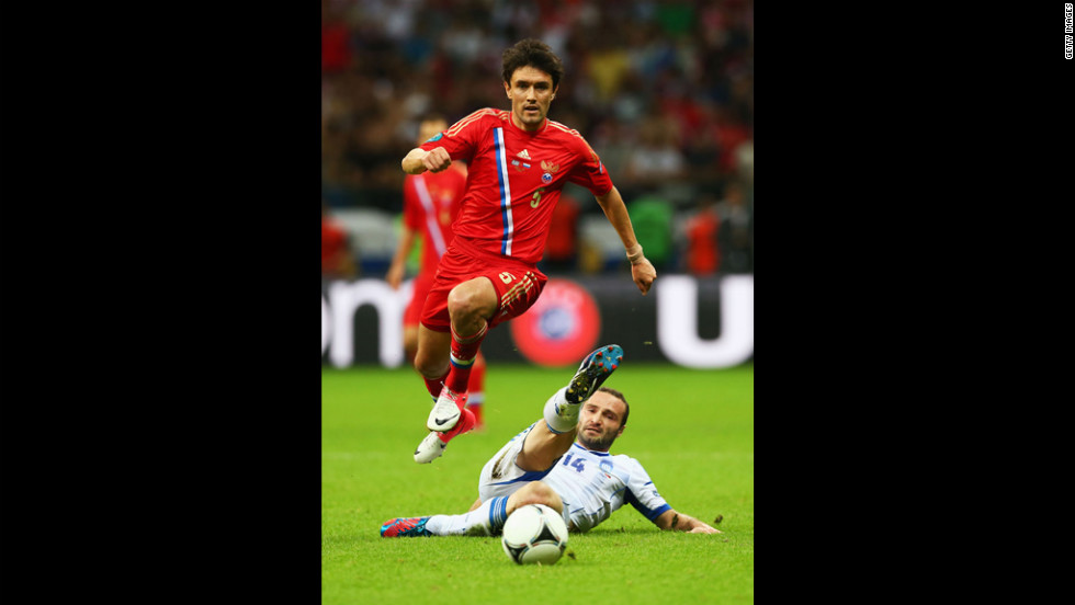 Yuriy Zhirkov of Russia jumps over the challenge by Dimitris Salpigidis of Greece during the match between Greece and Russia.