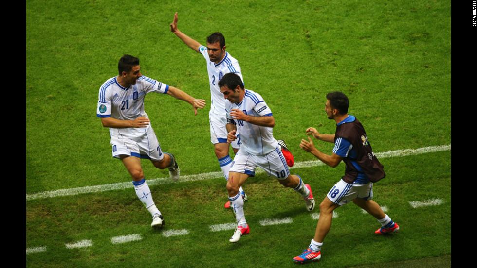 Giorgos Karagounis of Greece, center, celebrates scoring the opening goal with teammates, left to right, Kostas Katsouranis, Giannis Maniatis and Sotiris Ninis during the match between Greece and Russia.