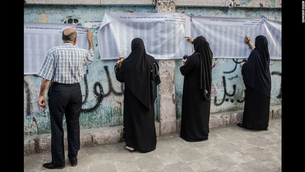 Egyptians check to see their names are listed before casting their votes at a polling station.