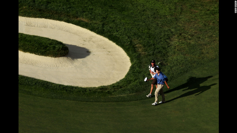 Amateur Beau Hossler of the United States walks to the 18th green with his caddie, Bill Schellenberg.