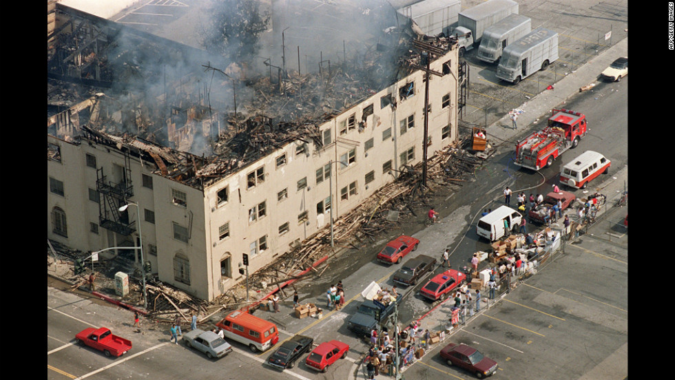People line the sidewalk across from a burned out apartment building that was destroyed in the violence. More than 1,100 buildings were destroyed or damaged during the riots.