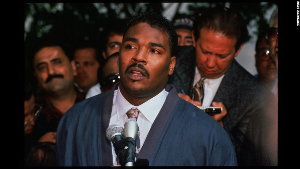 "Rodney King pleads for rioters to end the violence during a news conference in front of his lawyer's office on May 1 saying, ""People, I just want to say, can we all get along? Can we get along? Can we stop making it horrible for the older people and the kids?"""