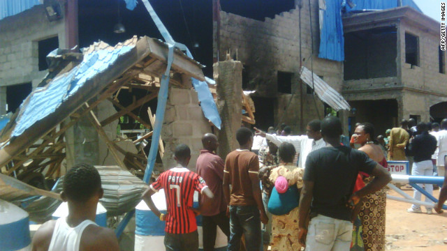 Bystanders outside Sharon Church after it was hit  by a suicide bomb attack in Kaduna, Nigeria,  on June 17, 2012.