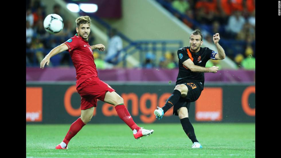 Rafael van der Vaart of the Netherlands scores the opening goal past Miguel Veloso of Portugal.