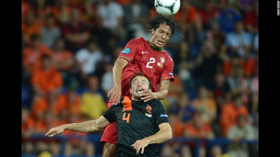 Portugal's Bruno Alves battles Joris Mathijsen of the Netherlands for control of the ball.