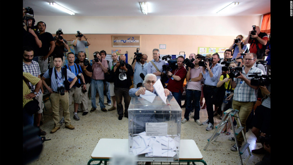 A woman, surrounded by media, casts her vote at a polling station in Athens.