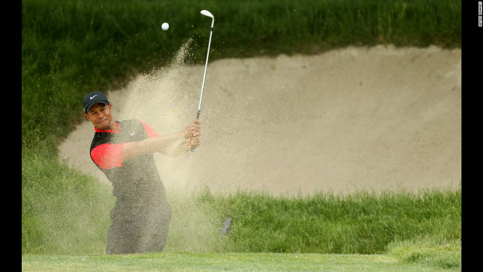 Tiger Woods hits a bunker shot on the first hole on Sunday.