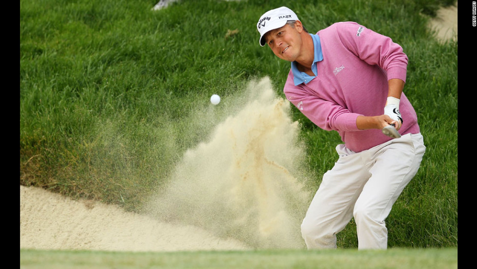 Fredrik Jacobson of Sweden plays a bunker shot on the second hole.
