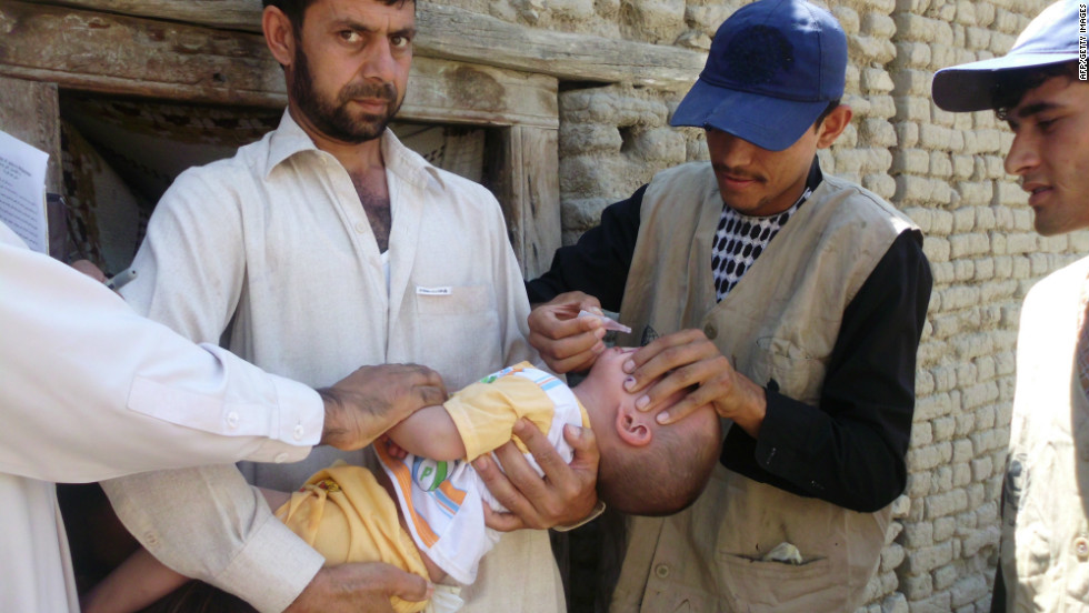 Afghan Health Ministry employees administer polio vaccine drops to a child in Laghman province on June 11, 2012.