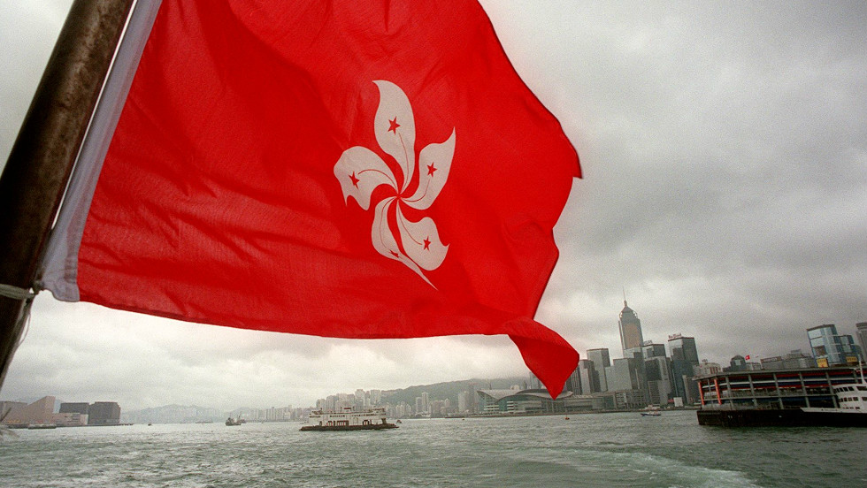 The new Hong Kong Special Administrative Region flag featuring a Bauhinia flower flies over the city from a ferry boat on July 2, 1997.