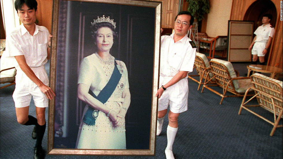 Two Royal Navy sailors remove a portrait of Queen Elizabeth II in HMS Tamar, the British Forces' Hong Kong headquarters, clearing the facilities for China's People's Liberation Army.