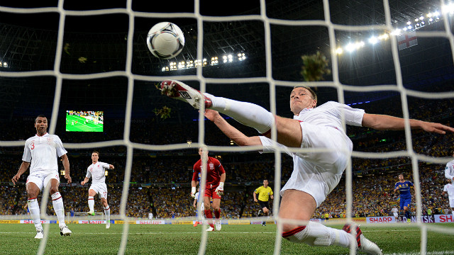 England's John Terry scrambles to clear an effort from Marko Devic which appeared to have crossed the line