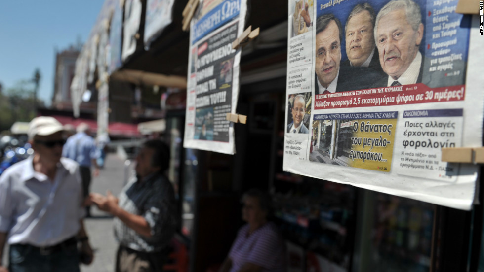 People read newspapers which detail the coalition talks on June 19. Greece hasn't had an elected government for 223 days.