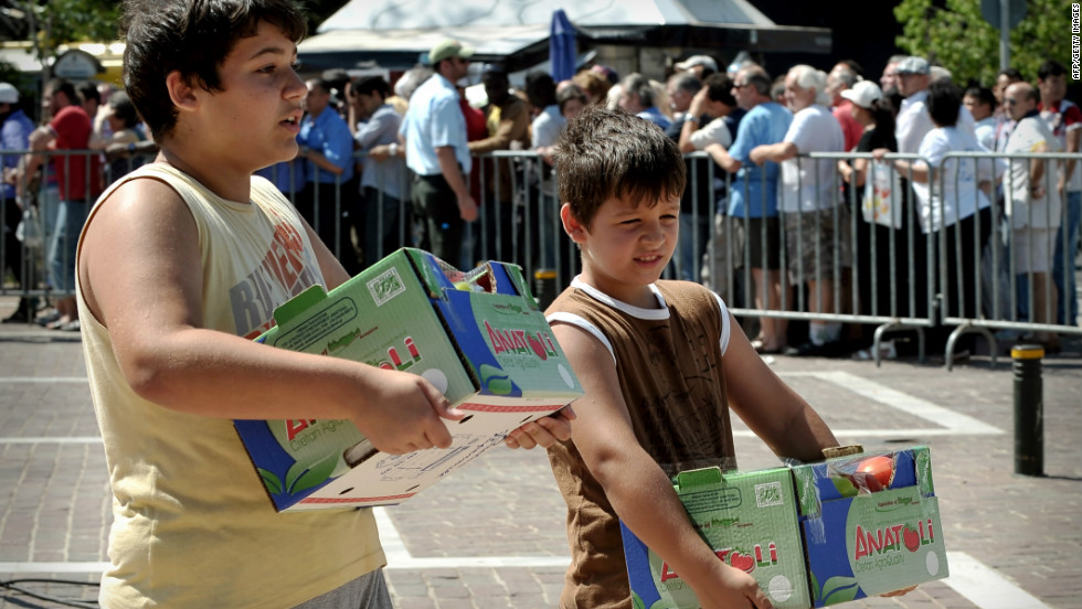 Children carry free vegetables donated by farmers from the Island of Crete in cooperation with the municipality of Athens, in Athens on June 20, 2012. The new coalition will have to deal with a devastating economic crisis.