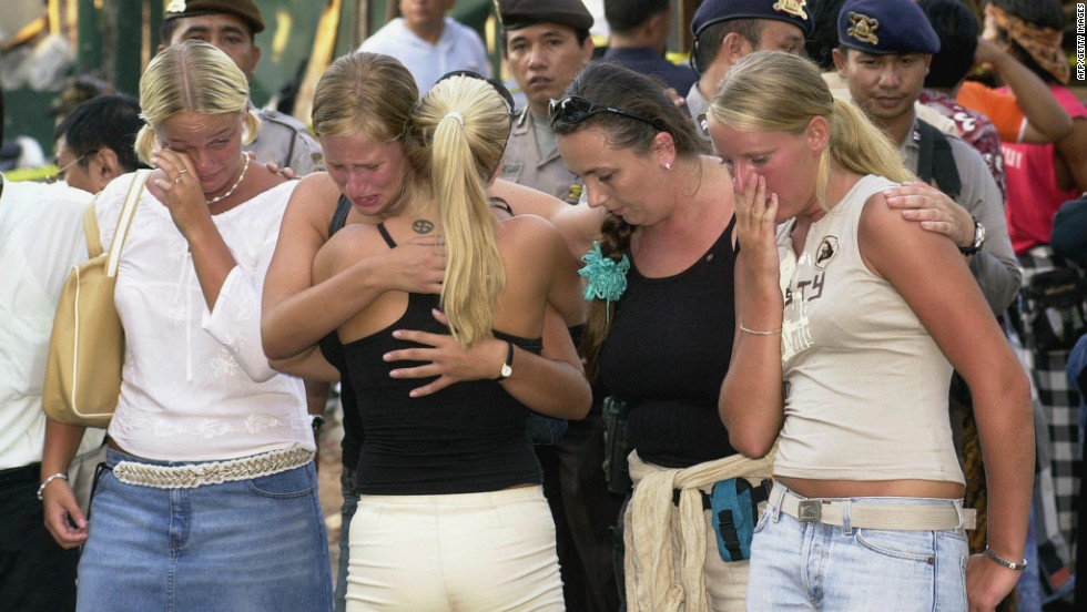 Several Australian women hug each other as they visit the blast site in the tourist area of Kuta, near Denpasar, on October 17, 2002.