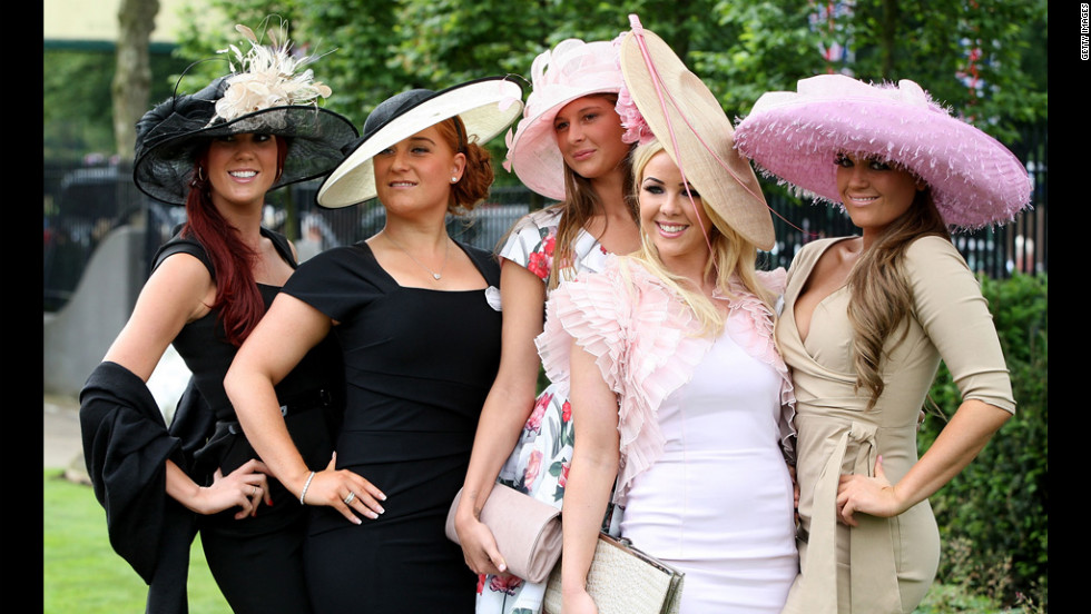 A group of women in striking hats poses for a photo.