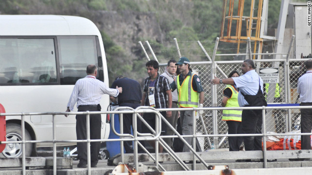 Rescued suspected asylum seekers arrive at Christmas Island after their boat capsized, on June 22.
