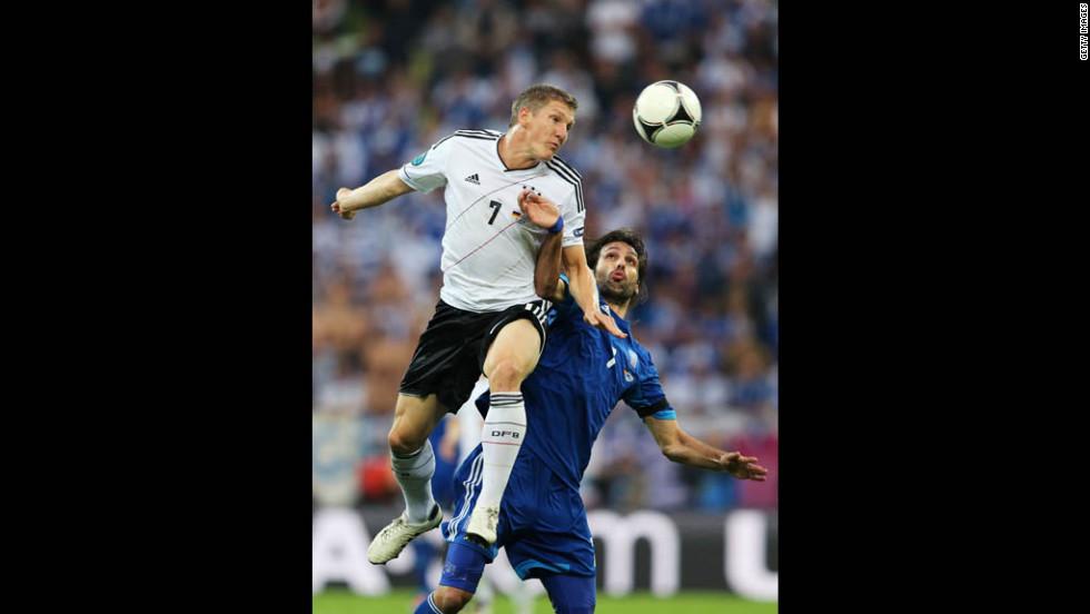 Germany's Bastian Schweinsteiger beats Greece's Georgios Samaras to the ball.