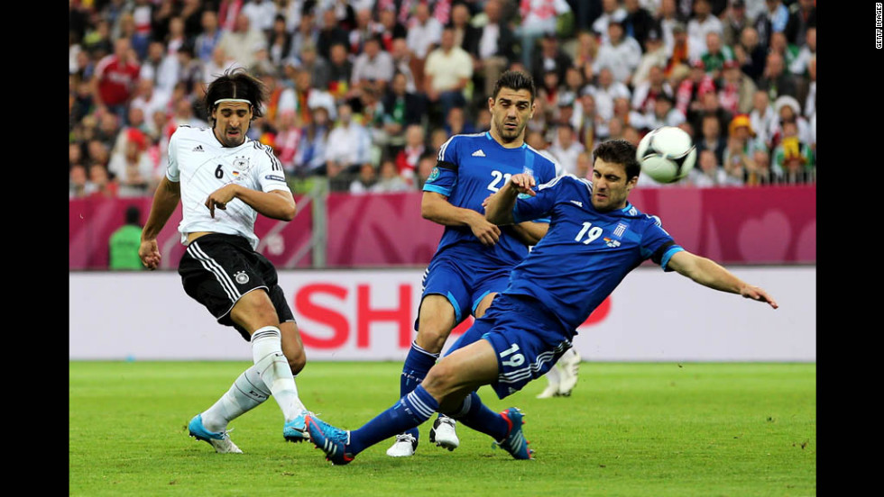 Greece's Sokratis Papastathopoulos and Germany's Sami Khedira compete for the ball.