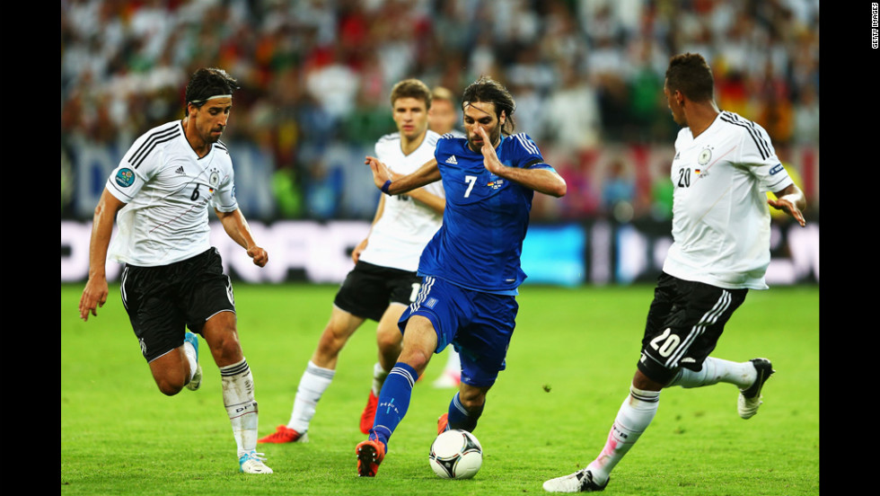 Georgios Samaras of Greece dribbles by Sami Khedira, left, and Jerome Boateng of Germany during the quarterfinal match between Germany and Greece.