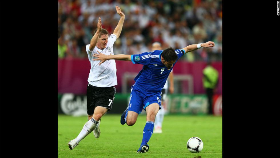 Bastian Schweinsteiger of Germany tackles Nikos Liberopoulos of Greece during the quarterfinal match between Germany and Greece.
