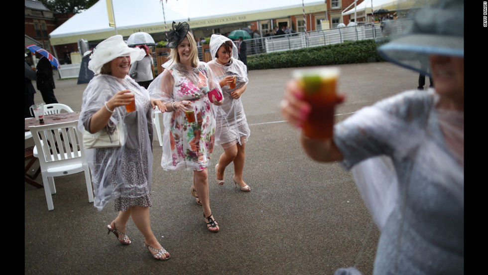Race-goers wear plastic rain covers over their dresses during some showers.